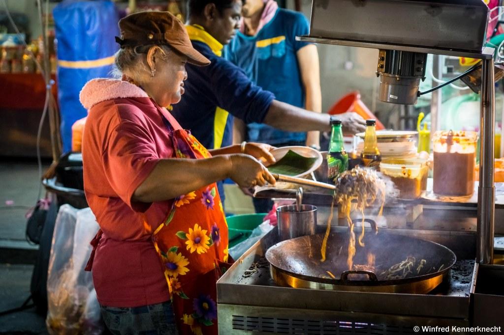 Auntie working the wok at Jonker Street Night Market, Melaka, Malaysia.