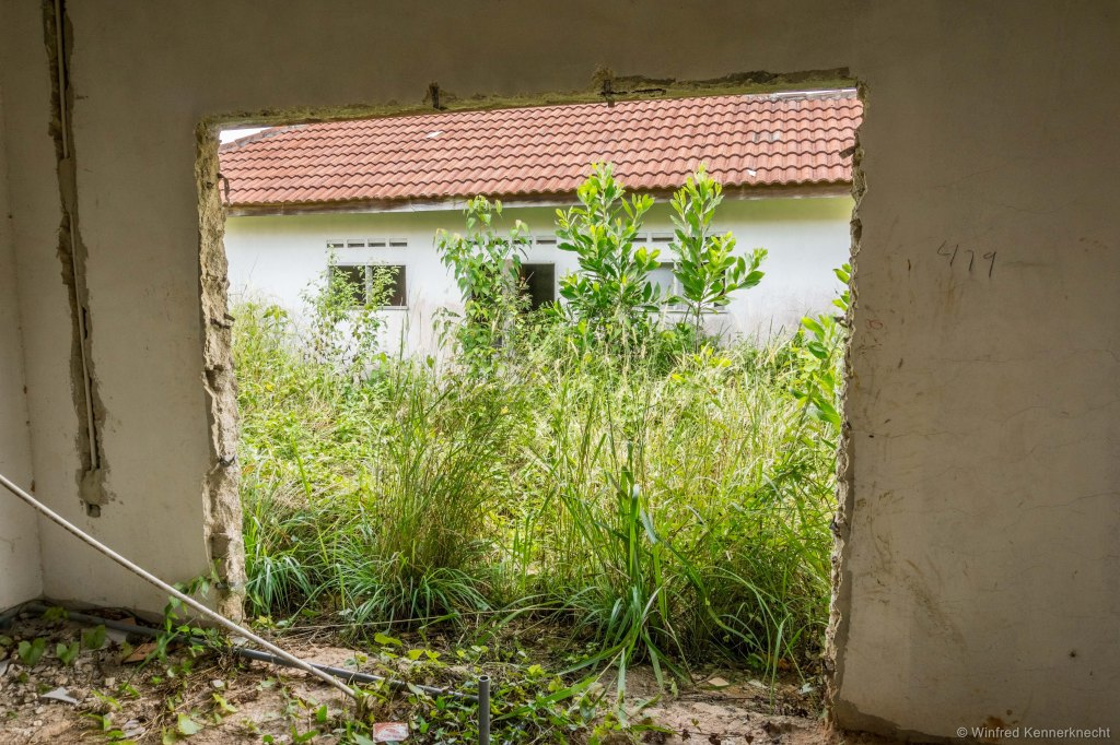 Opening in the wall on a ghost town house in Taman Sri Lambak T6, Kluang, Malaysia.
